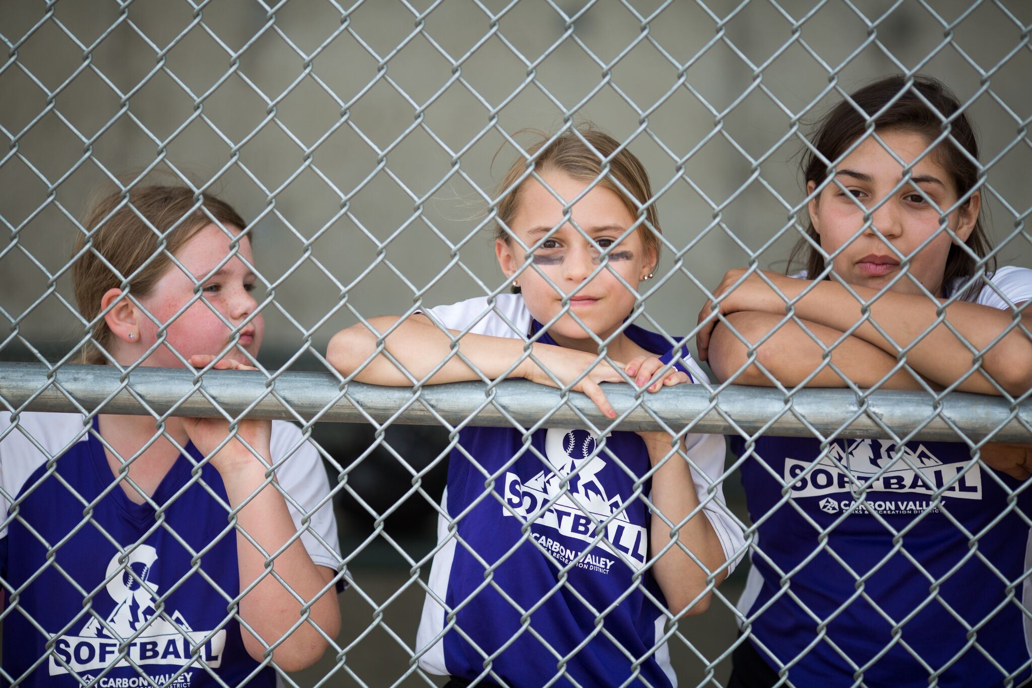 Three girls standing behind fence in dugout looking at fotball field.