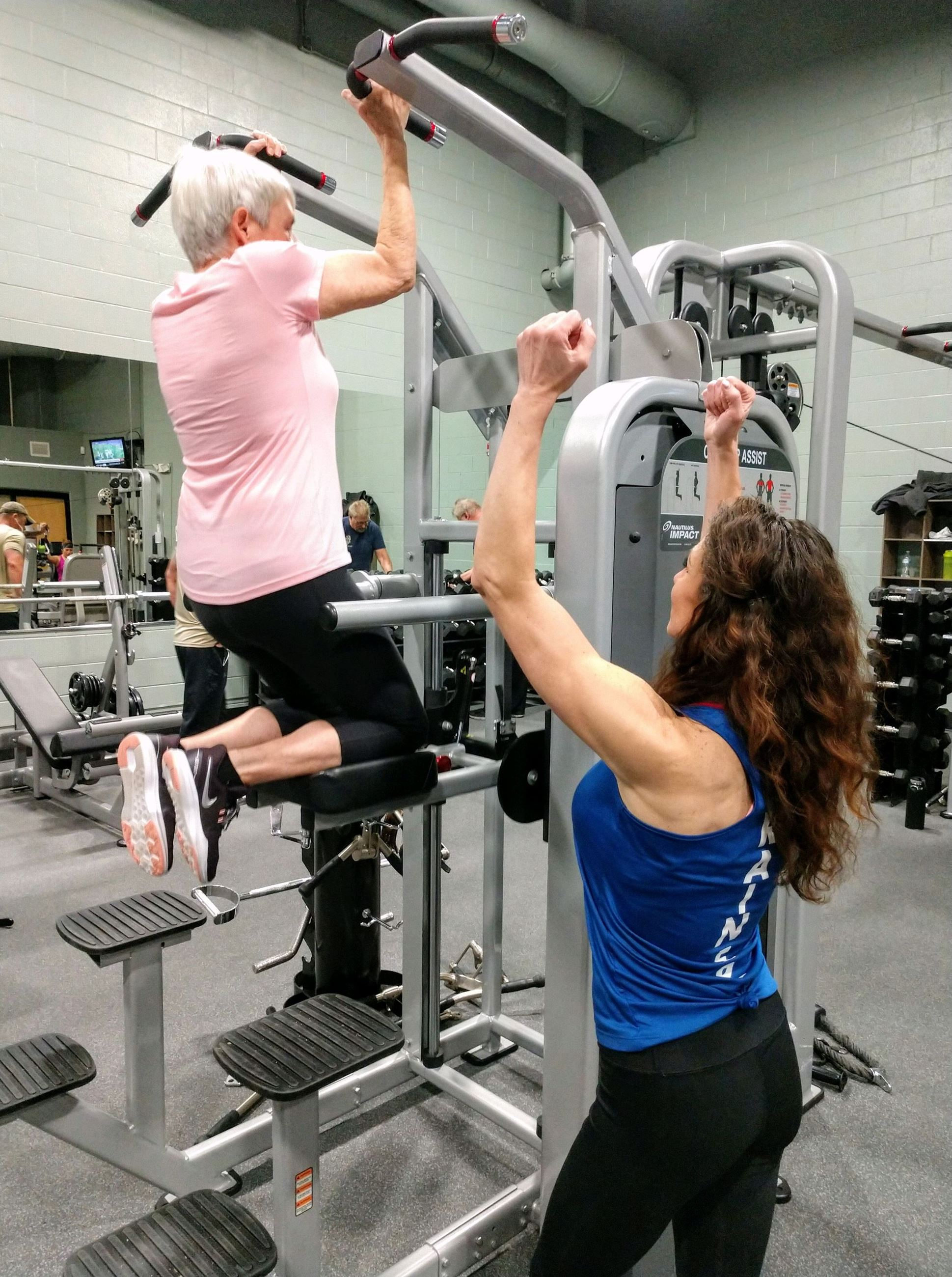 Female trainer helping woman train in gym.