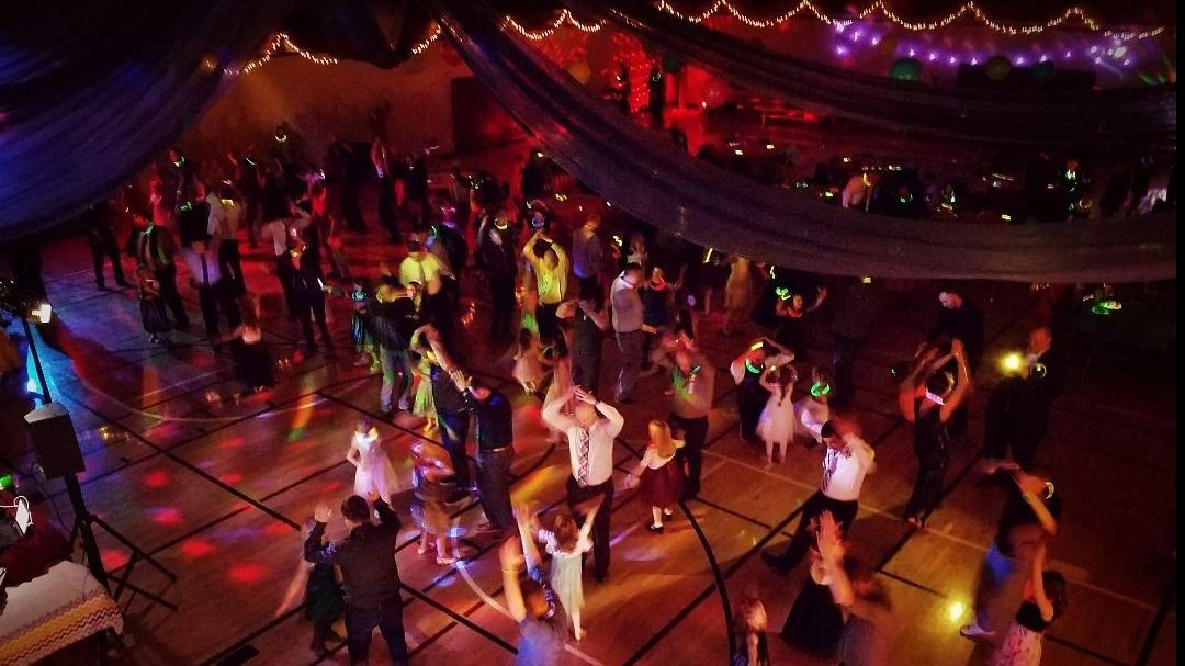 Dads and daughters dancing in a gym with colorful lights.