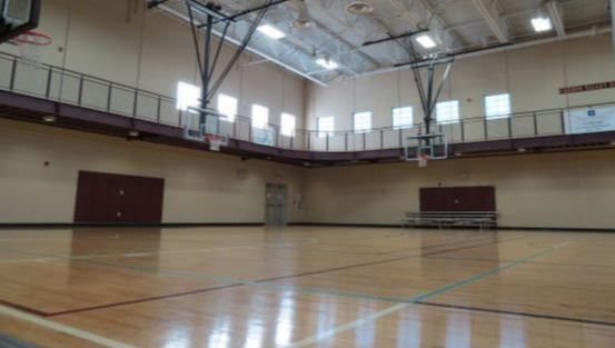 Empty gym with freshly waxed floor.