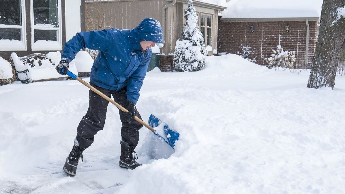 Man shoveling snow in front of house