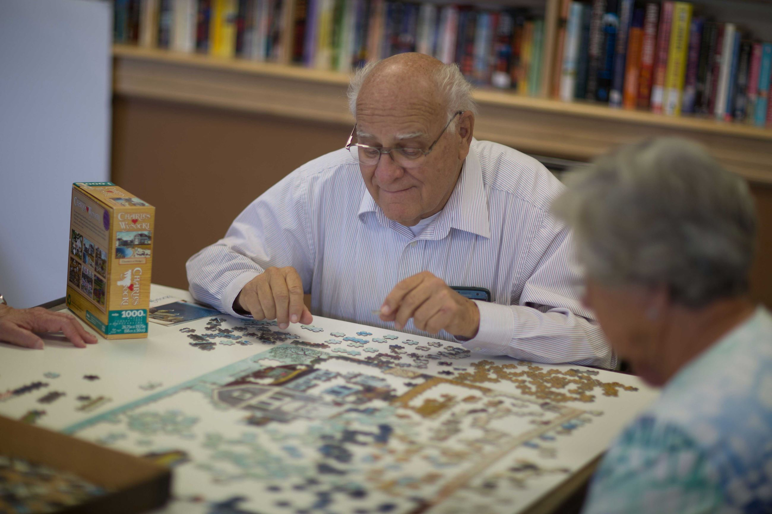 Senior male putting a puzzle together at a table in the Senior Center.