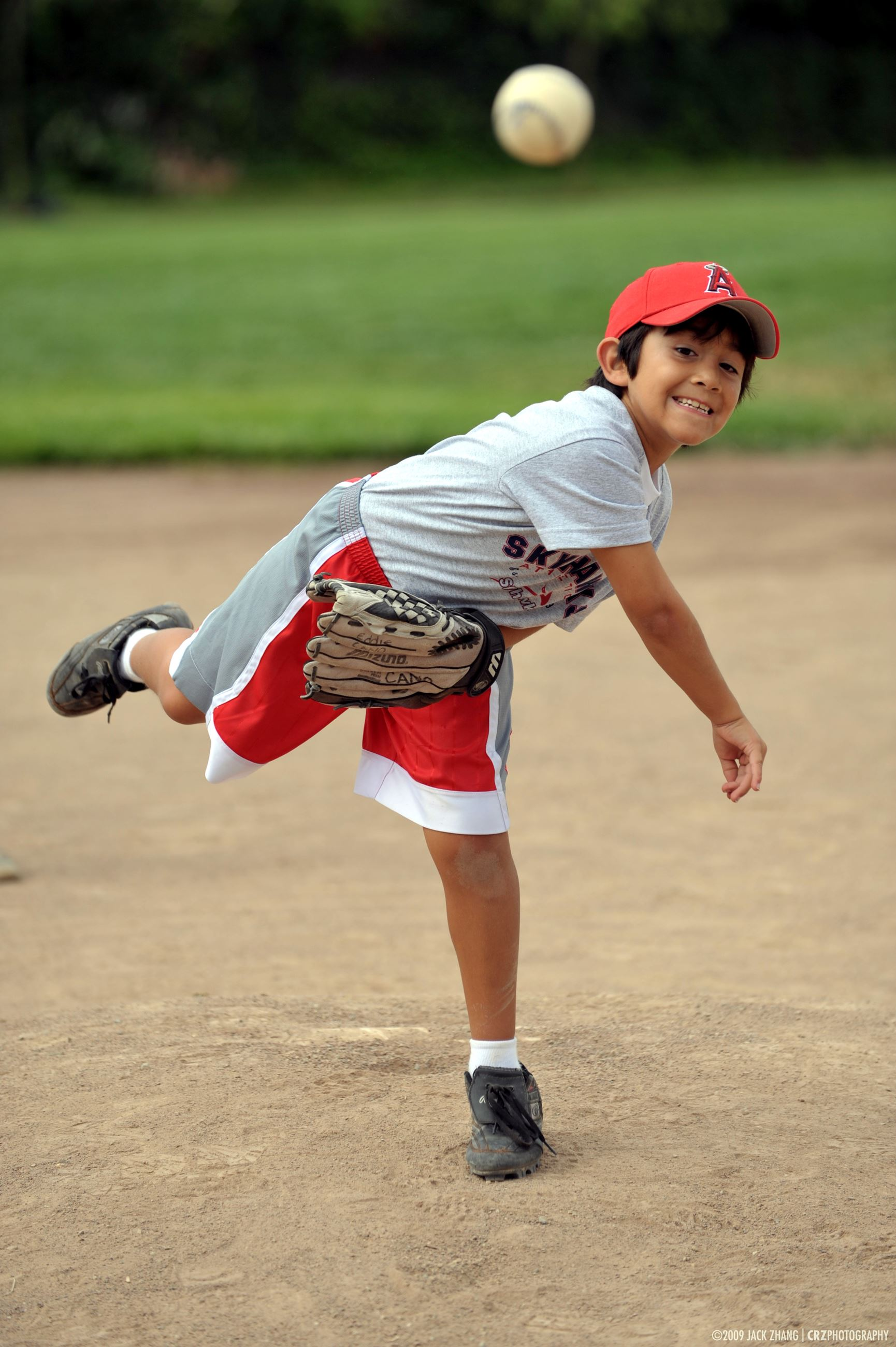 Boy pitcher throwing ball towards the camera
